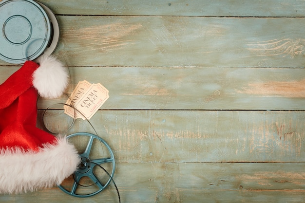 Christmas hat and cinema objects on wooden background