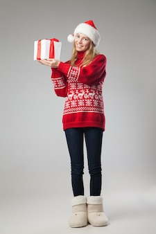 Рождественская шляпа изолированные женщина держит рождественский подарок