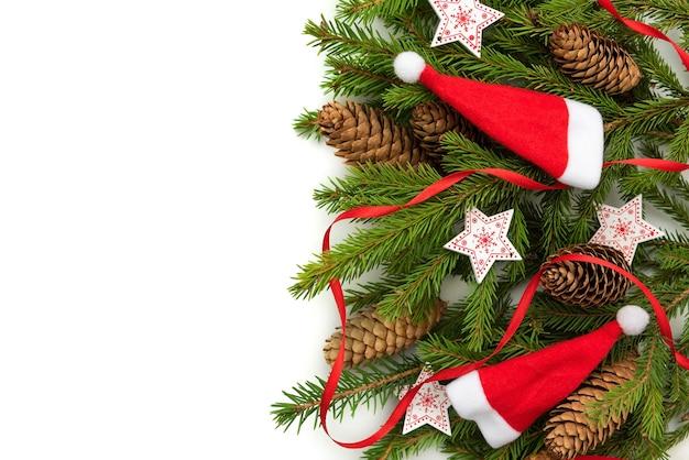 Рождественские шапки с еловыми ветками на белом фоне.