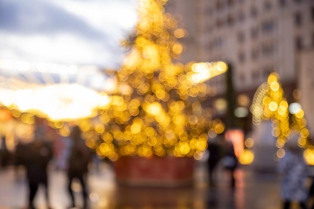 Рождественский праздник фон. рождественская елка в сияющей гирлянде на новогодней ярмарке на открытом воздухе в размытом виде