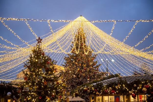 Рождественский праздник фон. новогодняя елка в сияющей гирлянде на новогодней ярмарке на уличном рынке