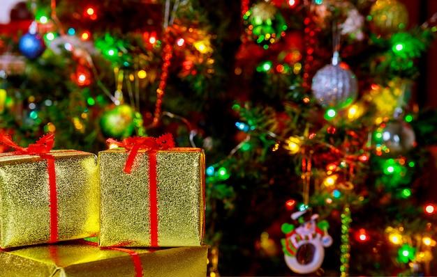 Рождественский праздник фон. подарки с красной ленточкой, елкой и декором