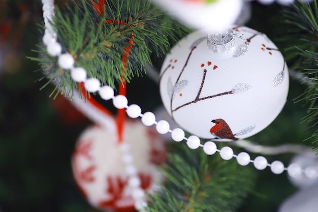 크리스마스 휴일 배경입니다. 보케와 눈으로 장식된 나무에 매달려 있는 은색과 컬러 보블은 공간을 복사합니다.
