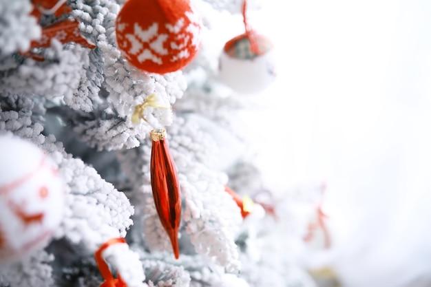 クリスマス休暇の背景。ボケと雪で飾られた木からぶら下がっている銀と色の安物の宝石、コピースペース。