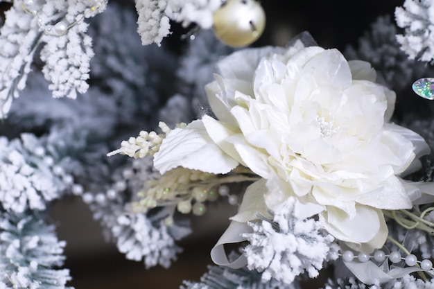 Christmas holiday background. silver and color bauble hanging from a decorated on tree with bokeh and snow, copy space.