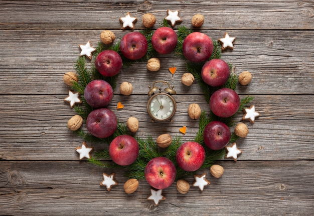 Christmas holiday background with  cookies, red apples, fir tree branches, vintage clock,