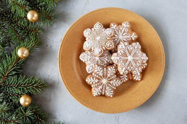 自家製の雪の結晶の形のジンジャーブレッドと、モミの木の枝とボールのクリスマス休暇の背景。平面図、クローズアップ、ライトグレーのコンクリートの背景。