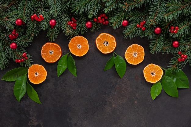 Christmas holiday background with fir-tree branches with red berries and balls, and fresh orange slices with green citrus leaves.
