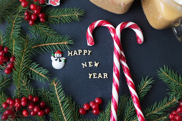 Christmas holiday background with hot cocoa and candy. the inscription happy new year.