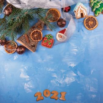 Рождественский праздник синий конкретный фон с еловыми ветками, игрушками гирляндой и украшениями. рождество и новогодняя тема. плоская планировка, вид сверху
