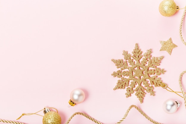 Christmas holiday composition. festive creative gold pattern, xmas golden decor holiday ball with ribbon, snowflakes on pink background. flat lay, top view