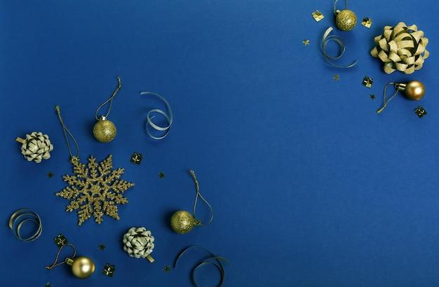 クリスマス休暇の構成。お祝いの創造的なゴールドシルバーパターン、リボン付きのクリスマスの装飾ホリデーボール、クラシックな青い背景の雪片。 2020年のクラシックブルーの色。フラットレイ、上面図