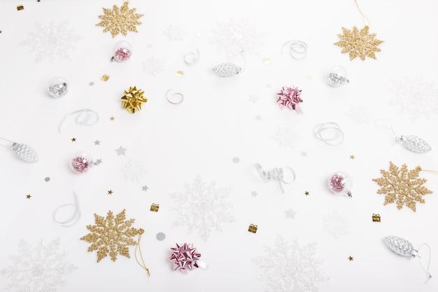 Рождественский праздник композиция. праздничный творческий золотой серебряный узор, рождественский розовый декор праздничный шар с лентой, снежинки на белом фоне. плоская планировка, вид сверху