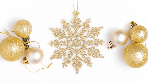 Christmas holiday composition. festive creative golden pattern, xmas gold decor holiday ball with ribbon, snowflakes, on white background. flat lay, top view, banner
