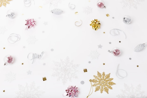 Christmas holiday composition. festive creative golden pink pattern, xmas decor holiday ball with ribbon, snowflakes on white background. flat lay, top view