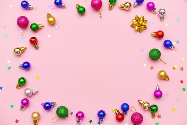 クリスマス休暇の構成。碑文、クリスマスのカラフルな装飾、お祝いのボール、ピンクの背景に雪片のための円の空きスペースの形でお祝いの創造的なパターン。フラットレイ、上面図