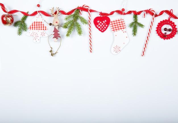 크리스마스 휴일 구성입니다. 축제 창조적 인 빨간색 패턴, 리본, 크리스마스 사탕 지팡이, 선물, 크리스마스 트리 및 흰색 배경에 빨간색 장식으로 크리스마스 수제 장식 휴일.