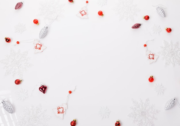 Christmas holiday composition. festive creative white red pattern, xmas decor holiday ball with ribbon, snowflakes on white background. flat lay, top view