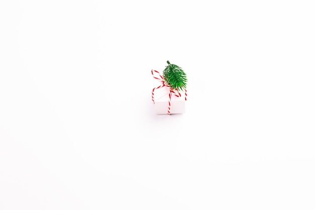 Рождественский праздник композиции подарочная коробка с еловой веткой на белом фоне. минималистичная концепция праздника