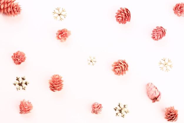 雪片とピンクのモミの実のクリスマス休暇の構成。ミニマルな休日のコンセプト