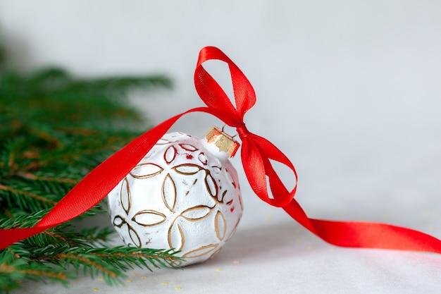 明るい背景に白いボールと赤いリボンのクリスマス休暇の構成