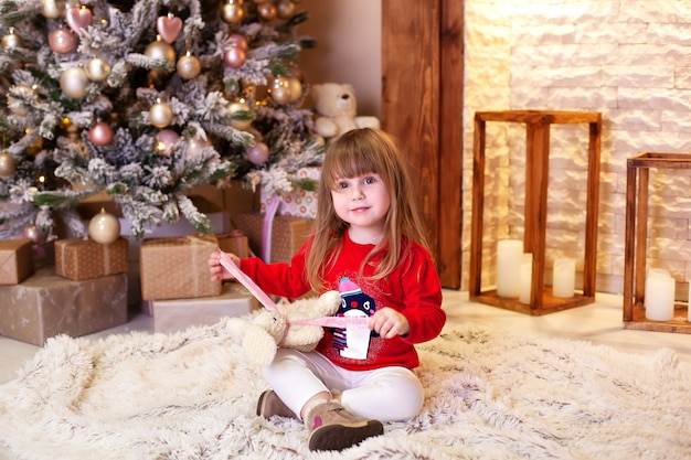 Christmas holiday concept. little girl in red sweater sitting by christmas tree with gift. child opens christmas present at home