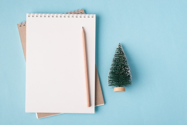 クリスマスの休日のコンセプト。上の俯瞰図フラットレイ写真空白のノートブックとコピースペースでパステルブルーの背景に分離された小さなクリスマスツリー