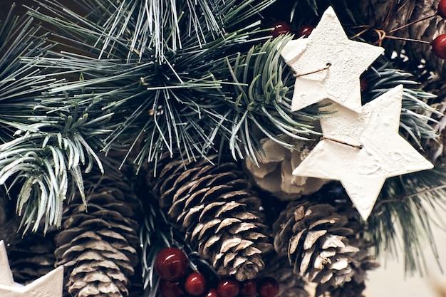 크리스마스 휴일 장식입니다. 크리스마스 전나무 브런치에는 붉은 열매, 스타 촛불, 눈이 반짝이는 콘이 질감을 더 가까이서 볼 수 있습니다. 얕은 초점. 크리스마스 세로 벽지 개념