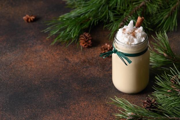 茶色の背景にシナモンで飾られたモミの木とメイソンジャーのクリスマスホリデーエッグノッグ