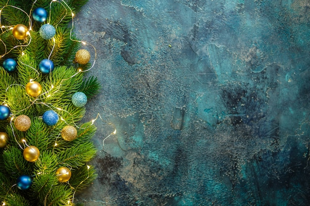 Christmas holiday frame with festive decorations blue and gold baubles on old blue. christmas with copy space