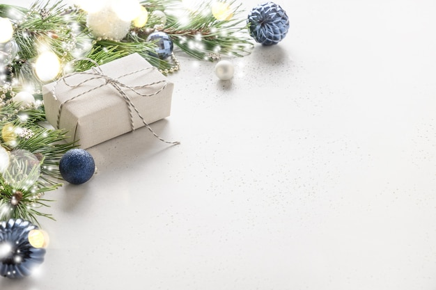 Рождественский праздничный подарок, синие безделушки и вечнозеленые ветви на белом.