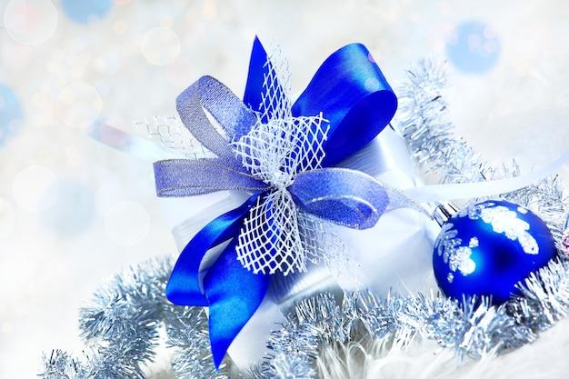 Рождественский праздничный подарок в красивой упаковке и синие стеклянные шары на праздничном фоне