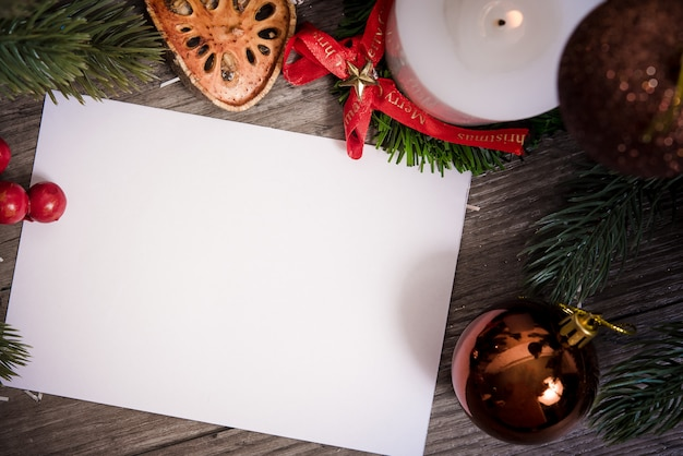 Christmas holiday greeting paper card design mockup with decoration on wood table.