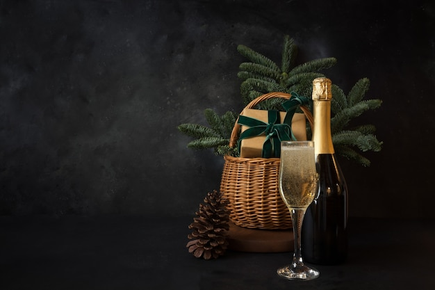 Christmas holiday hamper with glass of sparkling wine and gift on black space