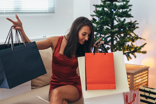Christmas holiday happy woman with shopping bags at home. new year