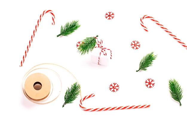 Макет праздника рождества. полосатые леденцы, еловые ветки, снежинки и подарочная коробка на белом фоне