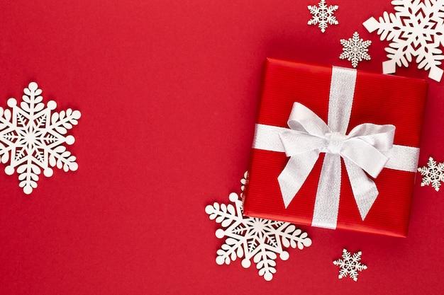 Рождество, праздничная подарочная коробка на красном фоне.