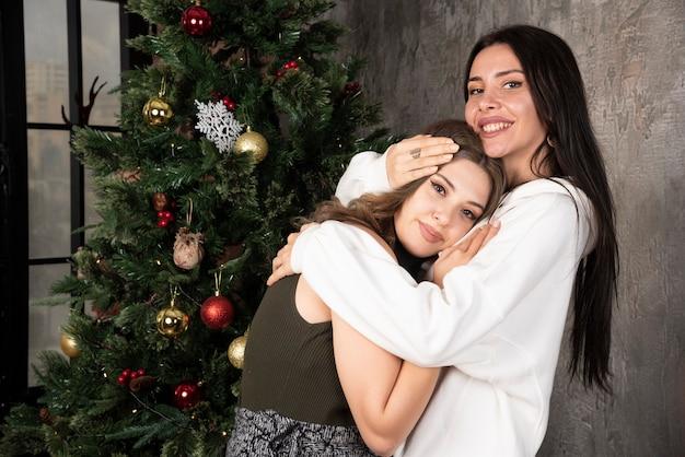 Рождественский праздник со счастливыми подругами, обнимающими друг друга в украшенной гостиной