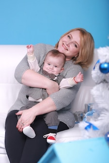 Christmas holiday. young grandmother with her little grandson on a white sofa near christmas tree. blue wall with a white moon and stars on a wall.