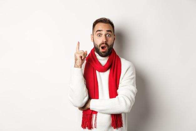 クリスマス休暇とお祝いのコンセプト。アイデアを持って、指を上げて計画を提案し、セーター、白い背景の赤いスカーフに立っている興奮したひげを生やした男。