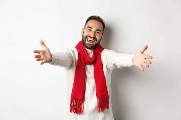 クリスマス休暇とお祝いのコンセプト。入って来るように誘う、挨拶または抱擁ジェスチャーで手を差し伸べる、幸せな新年を願って、白い背景の上に立っているフレンドリーな男
