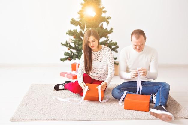 クリスマス、休日、お祝いのコンセプト-ハンサムな若い男とかなり若い女性がカーペットの上に座って、ギフトボックスを保持しています。