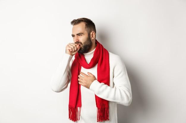 クリスマス休暇とお祝いのコンセプト。喉の痛みから気分が悪くなり、咳や顔をゆがめ、大晦日に19の症状が現れ、白い背景の上に立っている男性。