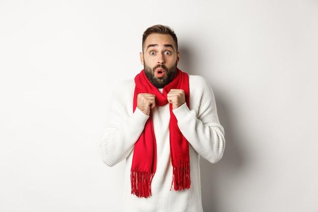 크리스마스 휴일 및 축 하 개념입니다. 카메라를 보고 놀란 남자, 새해에 추위를 느끼고 빨간색 스카프와 스웨터, 흰색 배경을 입고