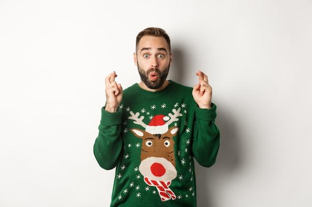 クリスマス、休日、お祝い。興奮した男が願い事をし、幸運と笑顔のために指を交差させて、白い背景の上に立ってください。
