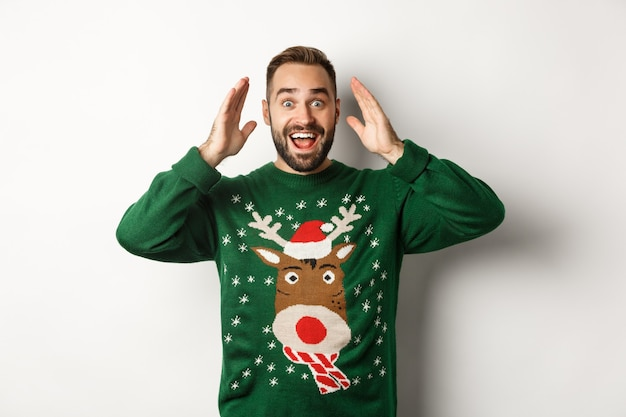 クリスマス、休日、お祝い。驚いた男は目を開けて贈り物を見て、白い背景に幸せに立っています。