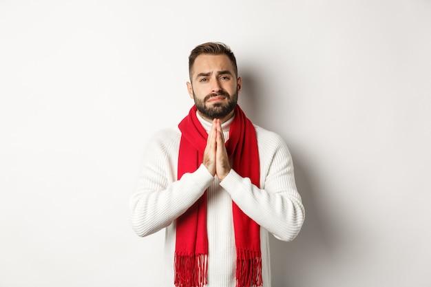 クリスマス休暇と新年のコンセプト。助けを懇願し、賛成を求め、祈りの中で手をつないで、カメラを希望を持って見て、白い背景の上に立っている絶望的な男。