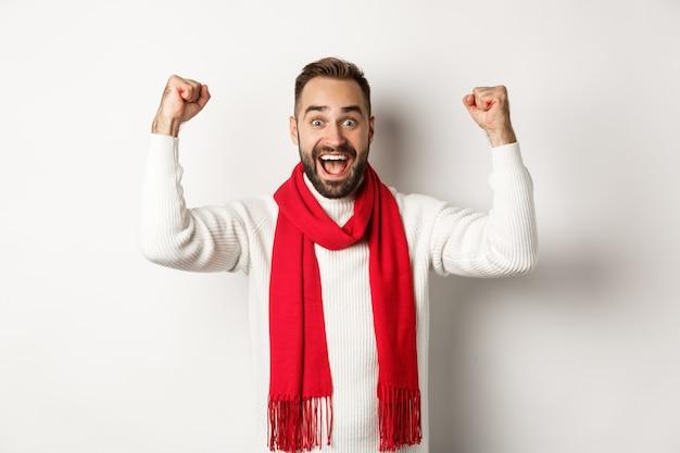 クリスマス休暇と新年のコンセプト。興奮した男は喜び、賞を獲得し、手を上げて安心し、勝利し、白い背景の上に立っています
