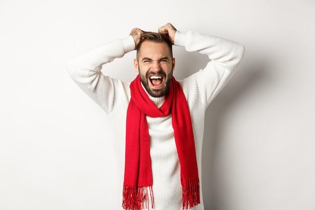 クリスマス休暇と新年のコンセプト。欲求不満と怒りの男は頭から髪を引っ張って苦しんで叫んで、白い背景に怒って立っている