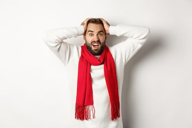 クリスマス休暇と新年のコンセプト。頭に手をつないで、パニックで叫び、白い背景に不安を抱いて立っている欲求不満の男